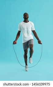 Workout. Sports man in sportswear exercising on jumping rope on blue background. Full length portrait of black male fitness model jump on skipping rope at studio