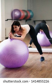 Workout, sports, training, healthy spine and active lifestyle. Sporty woman doing pilates exercise using sporting ball in gym