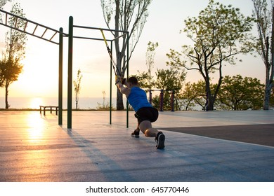 workout with suspension straps In the outdoor gym, strong man training early in morning on the park, sunrise or sunset in the sea background