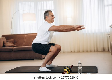 Workout time Strong senior man doing squat exercises at home in his light living room. Healthy lifestyle, wellbeing and activity concept. Black and white sportswear. Active and happy old age.