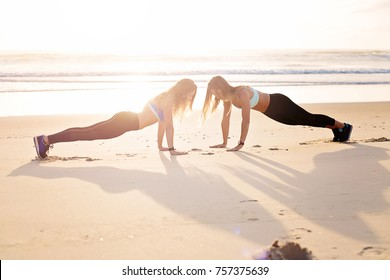 Workout together doing press ups on beach