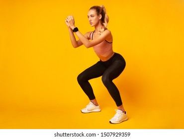 Workout. Young Woman Doing Deep Squat Exercise Over Yellow Studio Background. Copy Space
