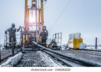 Workover rig working on a previously drilled well trying to restore production through repair. Toned