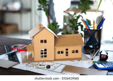 Arbeitsplatz des Architekten - Konstruktionszeichnungen, Maßstabsmodell und Werkzeuge. Modernes Hausdesign. Immobilienkonzept.