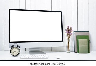 workplace background for designers with Blank white screen modern desktop computer, keyboard, book, alarm clock, flowera White wooden vintage background