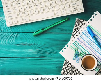 Workplace background with keyboard, notebook on dark green wooden background. Online blog concept