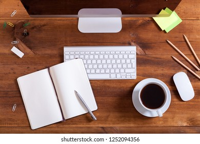 Workplace background, top above view of desk with desktop computer monitor keyboard open notebook with pen and coffee on brown wooden table, office supplies and business equipment for work concept