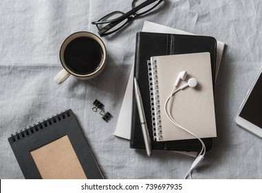 Workplace with a business, education, education accessories. Notepad, tablet, phone, headphones, pen, glasses, coffee on grey background, top view. Flat lay