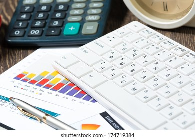 workplace businessman with keyboard, papers, calculator and clock