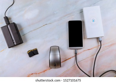 Workplace a charging phone in the powerbank on technology connect with cord cable copying photos from memory cards portable hard drive
