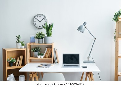 Workplace of contemporary office worker consisting of desk, lamp, copybooks, shelves with books and plants, gadgets and clock on wall