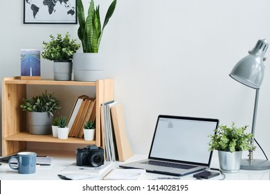 Workplace of contemporary stock photographer with photocamera, laptop, drink in mug and table lamp in office