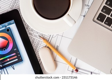 Workplace Designer, laptop, tablet and project with a pencil