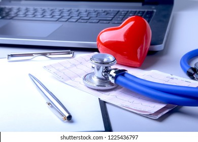 Workplace of doctor with laptop, stethoscope, red heart and RX prescription on white table. top view.