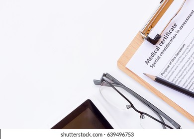 Workplace of a doctor. Medical certificate form,glasses,pencil and smart phone on wooden desk background. Top view with copy space. Healthy concept.