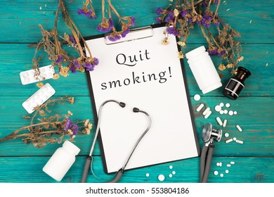 "Workplace of doctor - stethoscope, medicine clipboard with text ""Quit smoking!"", bottle and pills on blue wooden table"