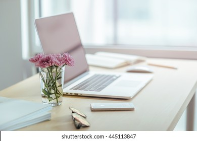 Workplace fashion blogger early in the morning. Modern desktop with laptop and spring flowers. Wooden desk with work stuff. Sunrise, Shallow DOF. Workplace in a skyscraper.
