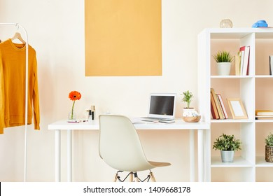 Workplace of fashion or interior designer by wall with desk, chair, cabinet with shelves and pullover on hanger in office or studio