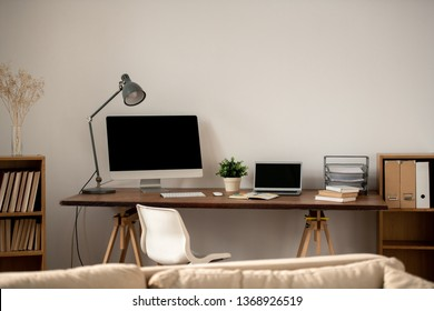Workplace of freelancer or home office employee with table against wall and number of supplies and gadgets for work