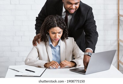 Workplace harassment concept. Boss touching his young attractive female assistant while she working on laptop at company office. Young woman suffering from offensive sexual behaviour