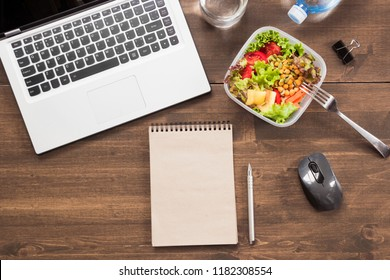 Workplace, healthy business lunch, salad, water on wooden table. Top view with copy space. Concept clean eating in office. To do list. Lunchbox.