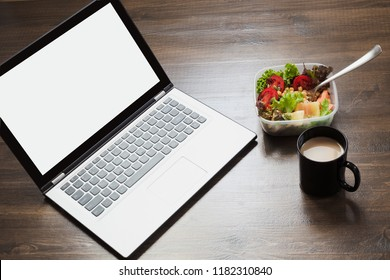 Workplace, healthy business lunch, salad, water on wooden table. Top view with copy space. Concept nutrition in office. To do list. Lunchbox.