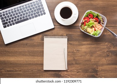 Workplace, healthy business lunch, salad, coffee on wooden table. Top view, copy space. Planning weight loss. To do list. Lunchbox