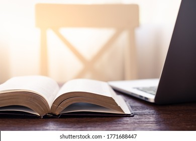 Workplace indoor with book or Holy Bible and laptop on the wooden desk