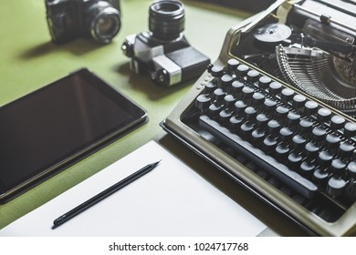 Workplace Of A Journalist, Writer, Blogger. Analog Typewriter, Digital Tablet And Film Camera On The Green Table
