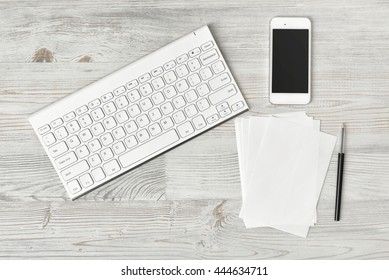 Workplace with keyboard, smarthphone, white sheets and pen on wooden surface in top view. Workplace of office man or information technology specialist. Office stuff. Readiness for the new. Beginning