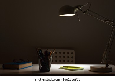 Workplace. The lamp in the dark with the light on, shines on the table.