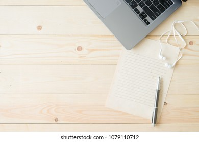 Workplace with laptop and blank notepad