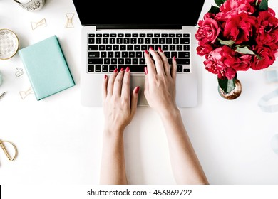 Workplace with laptop, girl's hands, peonies, golden scissors and diary. Flat lay composition for bloggers, magazines, social media and artists. Top view.