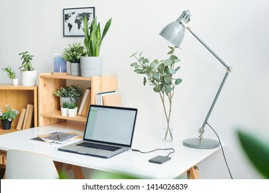 Workplace with laptop, lamp, books, copybooks, wooden shelves and green domestic plants in flowerpots and map picture on wall