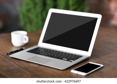 Workplace with laptop, mobile phone and cup of coffee indoors