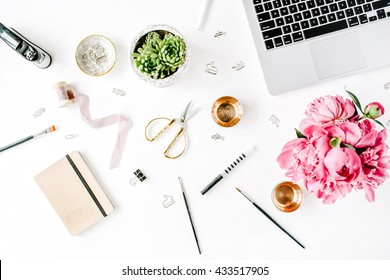 Workplace with laptop, succulent, peonies, golden scissors, spool with beige ribbon, pencils and diary. Flat lay composition for bloggers, magazines, social media and artists. Top view.
