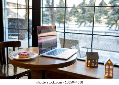 Workplace with a laptop. A table with a large window and a donut. Co-working. Workspace in a cozy coffee shop. It is snowing outside the window. Work on a laptop in winter