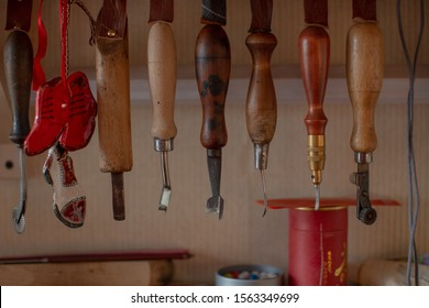 The workplace of a master shoemaker and his tools closeup are hanging on a shelf. Shoemaker's knife, awl, shoemaker's paw, hammer, hook and scissors, small red wooden boots