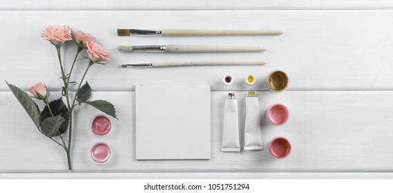 Workplace with miniature canvas, paintbrushes, roses and paints on wooden boards. Top view. Flat  design.