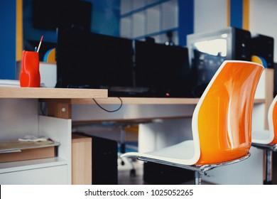 Workplace. Modern Chair in orange stands computer table