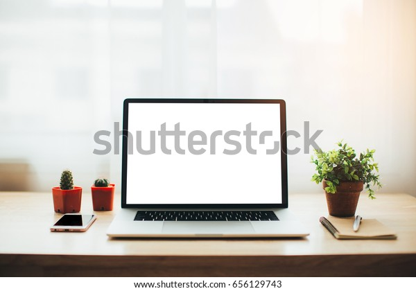 Workplace with modern laptop on table in the bedroom
