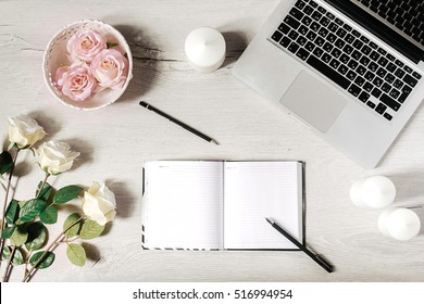 Workplace in modern style with laptop, diary, white candles, roses and wooden desk. Flat lay