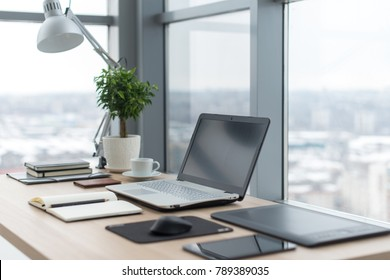 Workplace with notebook laptop Comfortable work table in office windows and city view.