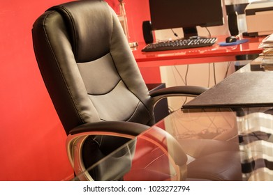 Workplace. Officce with black leather chair, glass table, computer and folders