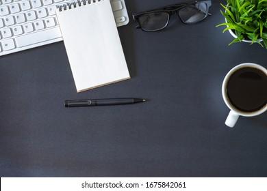Oficina en el lugar de trabajo con escritorio negro oscuro. Vista superior desde arriba del teclado con el bloc de notas y la taza de café. Espacio para la moderna obra creativa de diseño. Piso plano con espacio de copia. Concepto empresarial y financiero.