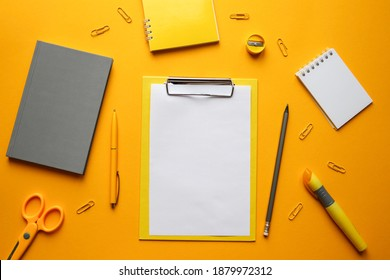 Workplace with office supplies on bright trendy yellow background. Blank sheet, pen, pencil, notepads, and other stationery. Top view, flat lay, mockup. Business and education concept