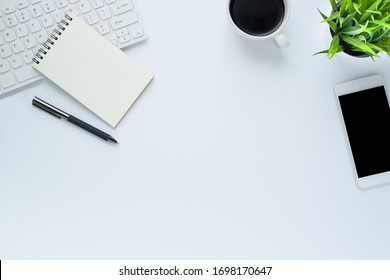 Workplace in the office with a white desk. Top view from above of keyboard with notebook and pen. Space for modern creative work of designer. Flat lay with copy space. Business and finance concept.