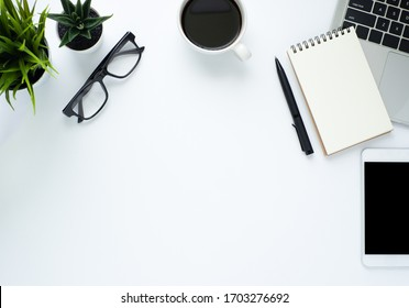 Workplace in office with white desk. Top view from above of laptop with notebook and coffee. Space for modern creative work of designer. Flat lay with blank copy space. Business and finance concept.