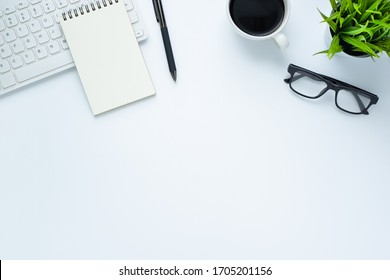 Workplace in office with white desk. Top view from above of keyboard with notebook and coffee. Space for modern creative work of designer. Flat lay with blank copy space. Business and finance concept.
