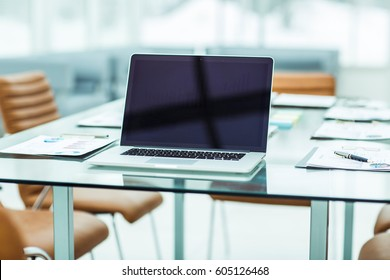 workplace with open laptop and financial documents prepared for meeting business partners